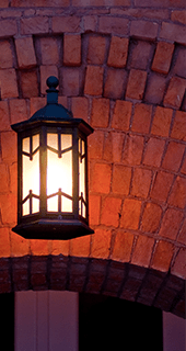 Lit hooded lantern hanging in front of a red brick wall